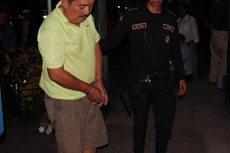 Juan Gelber Solís Contreras, de 54 años, es custodiado por un agente de la PNC. (Foto Prensa Libre: Enrique Paredes)