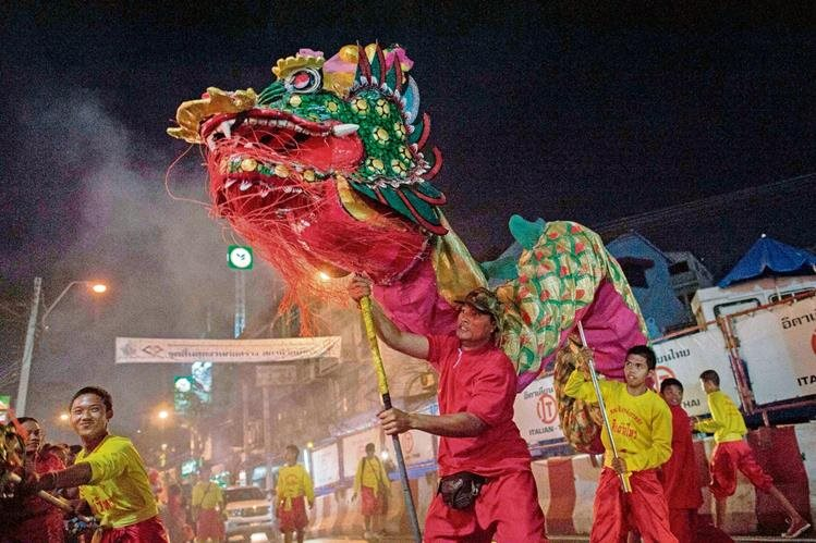 Un tailandés maneja un dragón gitante de papel durante la víspera del Año Nuevo de la Cabra en Bangkok