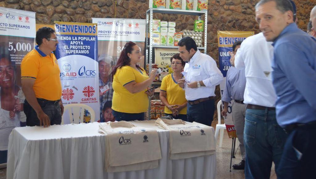 El presidente Jimmy Morales se informa de cómo es el proceso para  que las familias obtengan el beneficio. (Foto Prensa Libre: Víctor Gómez).