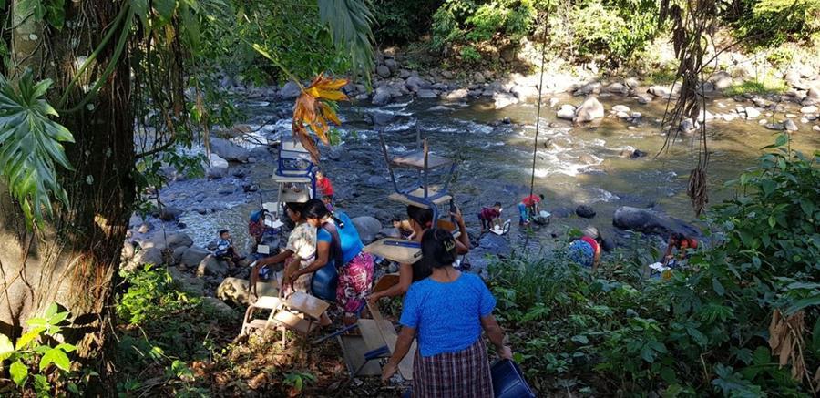 Ante la falta de agua entubada en el establecimiento, los escritorios fueron lavados en el río. (Foto Prensa Libre: Cristian Soto)