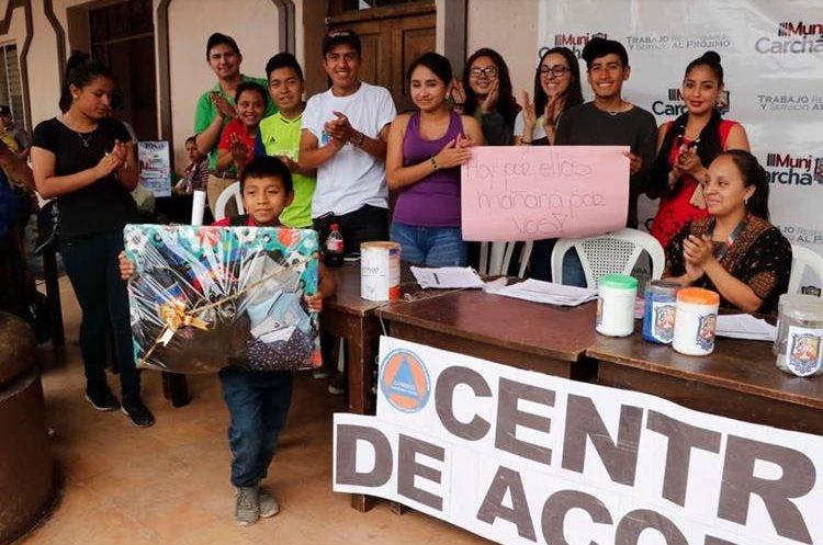 Personas del centro de acopio no desaprovecharon para tomarse una foto con el niño solidario. (Foto Prensa Libre: Eduardo Sam)