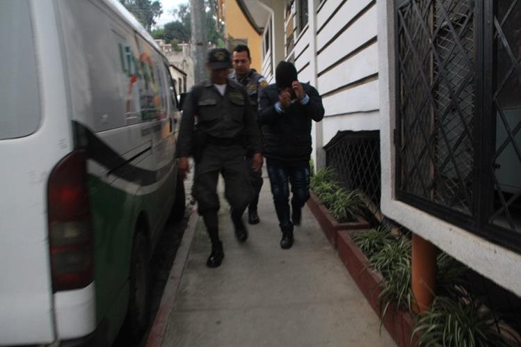 Juan Carlos Bixcul Peneleu, derecha, es custodiado por guardias del Sistema Penitenciario cuando sale del Tribunal de Sentencia de Femicidio de Sololá. (Foto Prensa Libre: Ángel Julajuj)