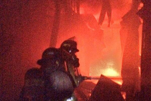 <p>Socorristas combaten las llamas entre los locales. (Foto Prensa Libre: CBM)</p>