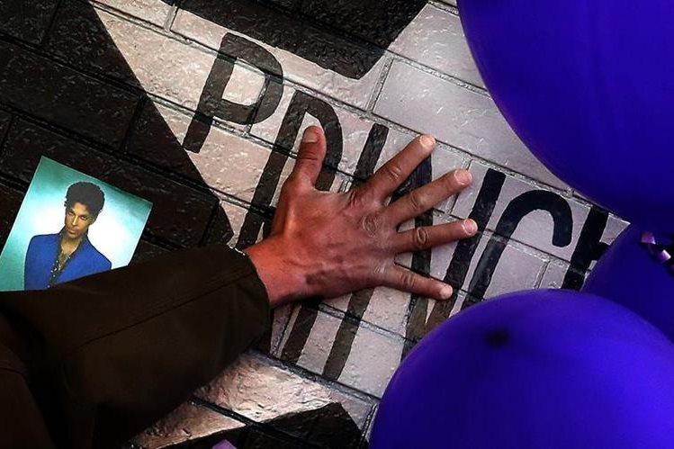 Un admirador de Prince, toca la estrella del artista en la Primera Avenida de Minneapolis, donde solía presentarse. (Foto Prensa Libre, AP)