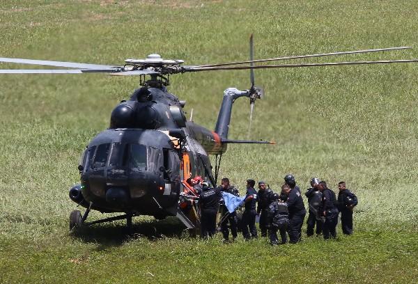 Un policía antidisturbios herido es trasladado a helicóptero en Oaxaca.(AP).