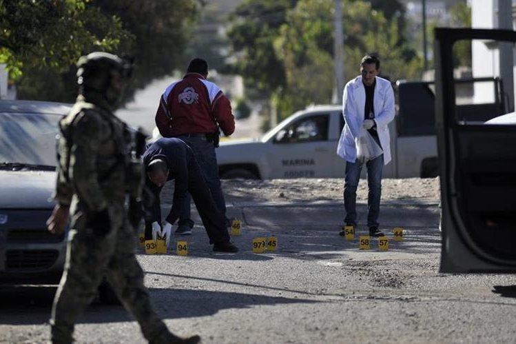 Forenses mexicanos recaban evidencias en el lugar del enfrentamiento armado. (Foto Prensa Libre: AFP)