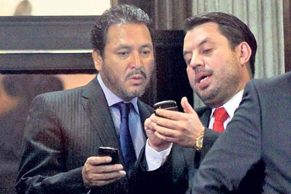 Gudy Rivera, del PP, actualmente en prisión por tráfico de influencias y Salvador Baldizón, de Líder, revisan información durante la elección de la CSJ, en septiembre de 2014. (Foto Prensa Libre: Hemeroteca PL)