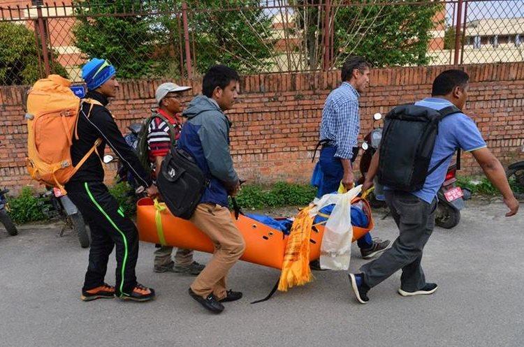 Voluntarios y amigos de Ueli Steck cargan su cuerpo hacía el hospital de Katmandú. (Foto Prensa Libre: AFP)