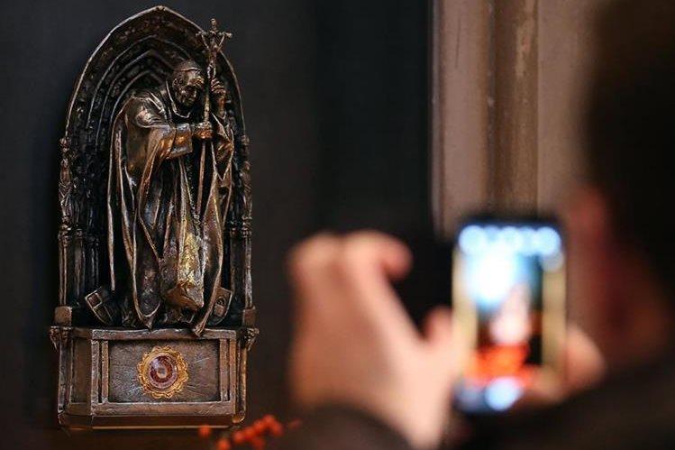 Un turista toma una fotografía a la reliquia de Juan Pablo Segundo, de cuyo interior fue extraído el trozo de tela en Colonia. (Foto Prensa Libre: AP).