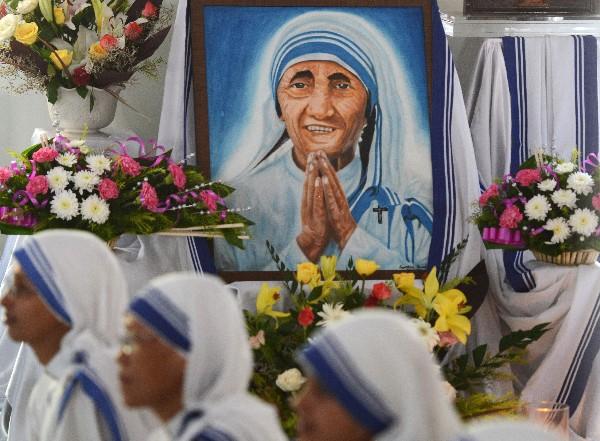 Fieles y monjas indias colocan flores a un retrato de la Madre Teresa en Siliguri. (AFP).