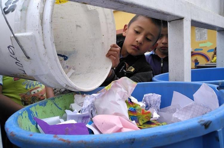 Un niño de la Escuela Oficial Urbana Mixta de San José Chacayá tira la basura en los recipientes identificados. (Foto Prensa Libre: Ángel Julajuj)
