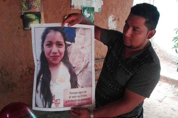 Un vecino sostiene una foto de Ángela Santiago Hernández de 12 años. (Foto Prensa Libre: Mario Morales)