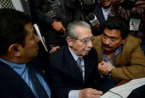Uno de los abogados tranquiliza al ex jefe de Estado, Efraín Ríos Montt durante la lectura de la sentencia. (Foto Prensa Libre: AFP)