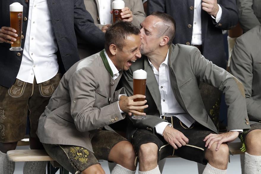 Rafinha recibe un beso de su compañero de equipo Franck Ribery usando ropa tradicional bávara. (Foto Prensa Libre: AP)