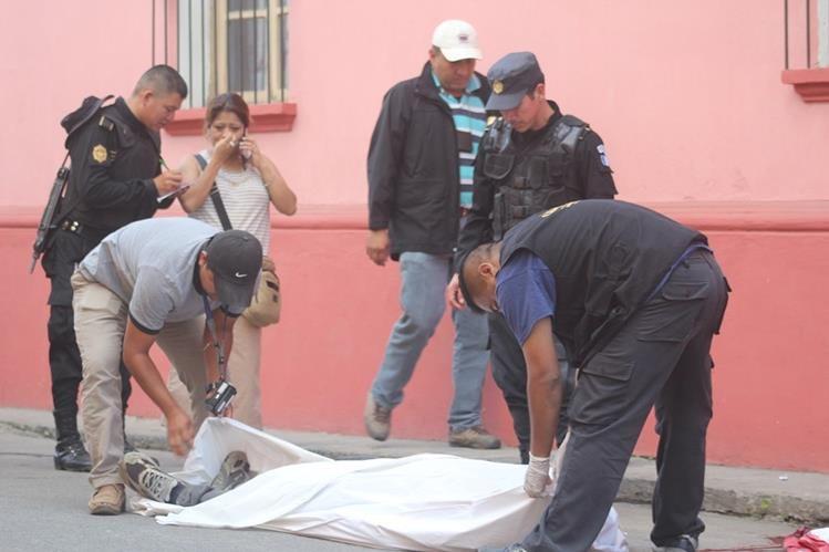 Fiscales del Ministerio Público cubren el cuerpo del maestro Nejimías Jonatán Salinas, el cual quedó a pocos metros de su negocio ubicado en la zona 3 de Cobán, Alta Verapaz. (Foto Prensa Libre: Ángel Tax)