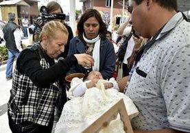 Una bebé recibe la bendición de su madrina Enriqueta Vargas (i), durante una celebración a la Santa Muerte en Tultitlan, Mexico. (Foto Prensa Libre: AFP).