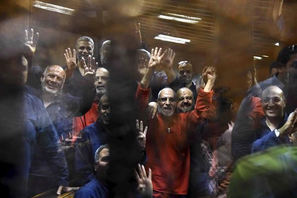<em>Miembros de los Hermanos Musulmanes, son fotografiados en la celda de acusados durante la lectura del veredicto contra Murso en El Cairo, Egipto, el martes 16 de junio. </em>