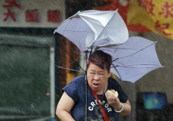 Una mujer luchas con su paraguas contra el fuerte viento generadas por el tifón Megi.(Foto Prensa Libre;AP).