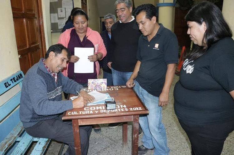Walfred Moreira, concejal primero, firma documento que será entregado a los demás ediles sobre la renuncia del alcalde. (Foto Prensa Libre: Víctor Chamalé)