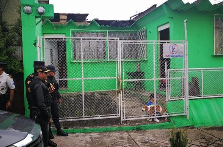 Un niño juega con su perro mientras las fuerzas de seguridad esperan afuera para realizar el allanamiento de una vivienda. (Foto Prensa Libre: Redacción)