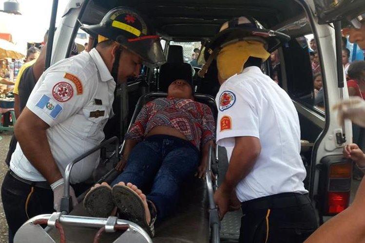 Socorristas trasladan a mujer embarazada que resultó golpeada por la carga de un autobús en Jalapa. (Foto Prensa Libre: Hugo Oliva)