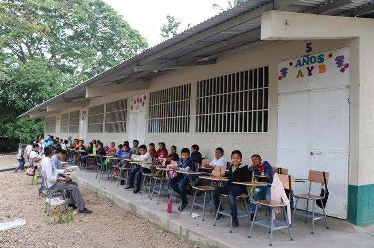 Un grupo de estudiantes de la Escuela Tres de Abril Gregorio Cocón Escalera en San Benito, Petén, reciben clases en el corredor, debido a que los salones están  deteriorados. (Foto Prensa Libre: Rigoberto Escobar)