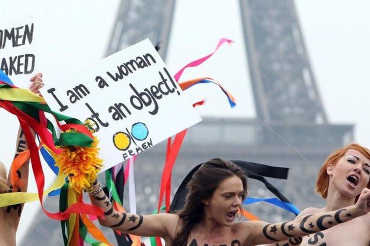Foto tomada el 31 de marzo de 2012, Oksana Shachko (C) con activistas topless del movimiento de Femen sostiene carteles mientras protestan en la torre Eiffel en París.(Foto Prensa Libre:AFP).