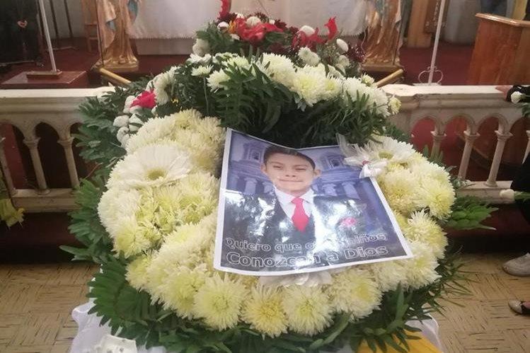 En el ataúd del adolescente los familiares colocaron su fotografía y ofrendas florales para honrar su memoria. (Foto Prensa Libre: Fred Rivera)