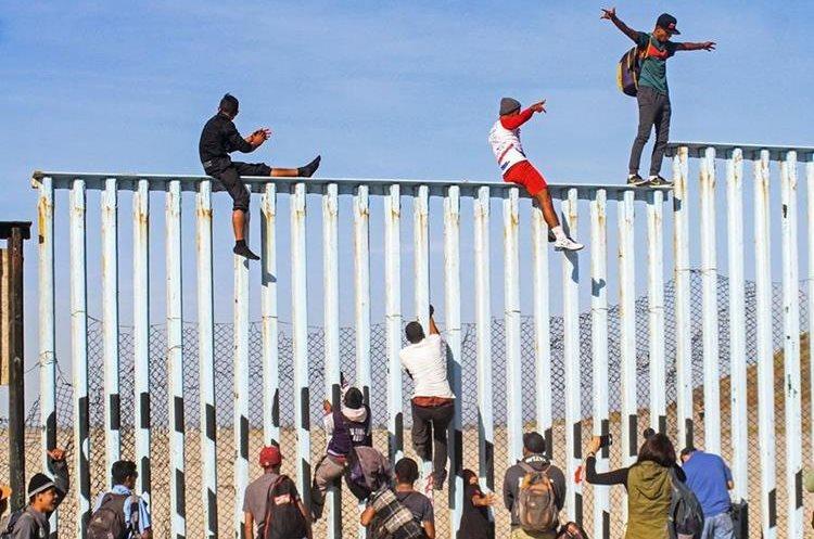 Decenas de migrantes centroamericanos alcanzaron la frontera México-Estados Unidos y treparon la valla que divide ambos países en una especie de primera meta en su objetivo final.