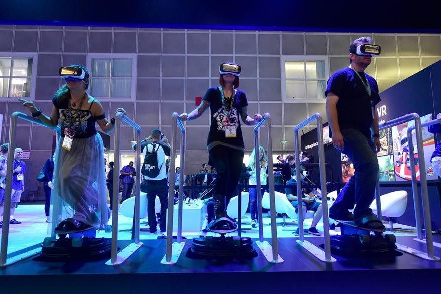 Asistentes al D3 patinan en un videojuego con los cascos Samsung Gear VR. (Foto Prensa Libre: AFP).