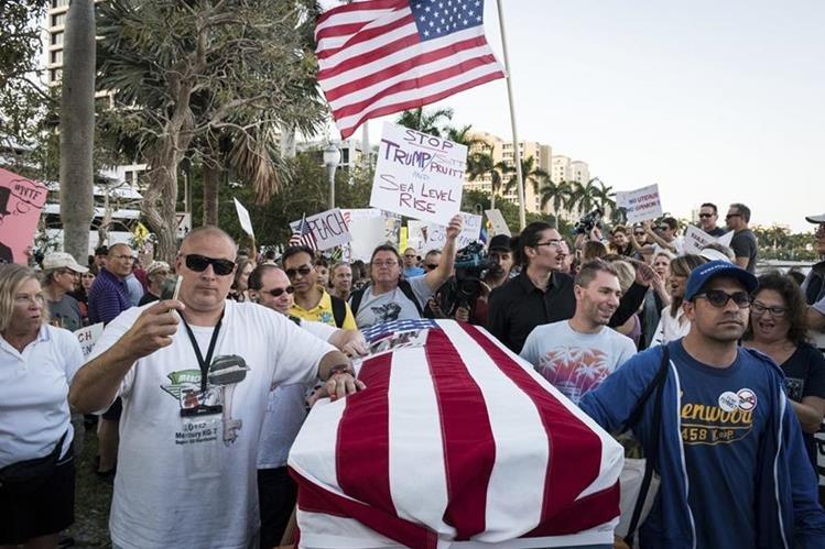 """En Florida, durante la visita de Trump, activistas simulan la """"muerte de la democracia"""". (Foto Prensa Libre: AP)"""