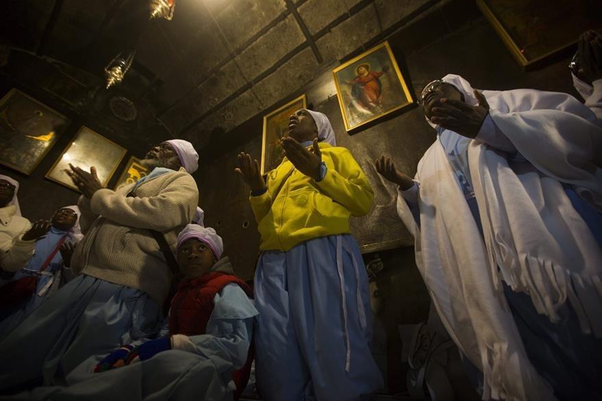 Peregrinas nigerianas oran  ante la gruta en la que nació Jesús, en Belén, Cisjordania. (EFE)