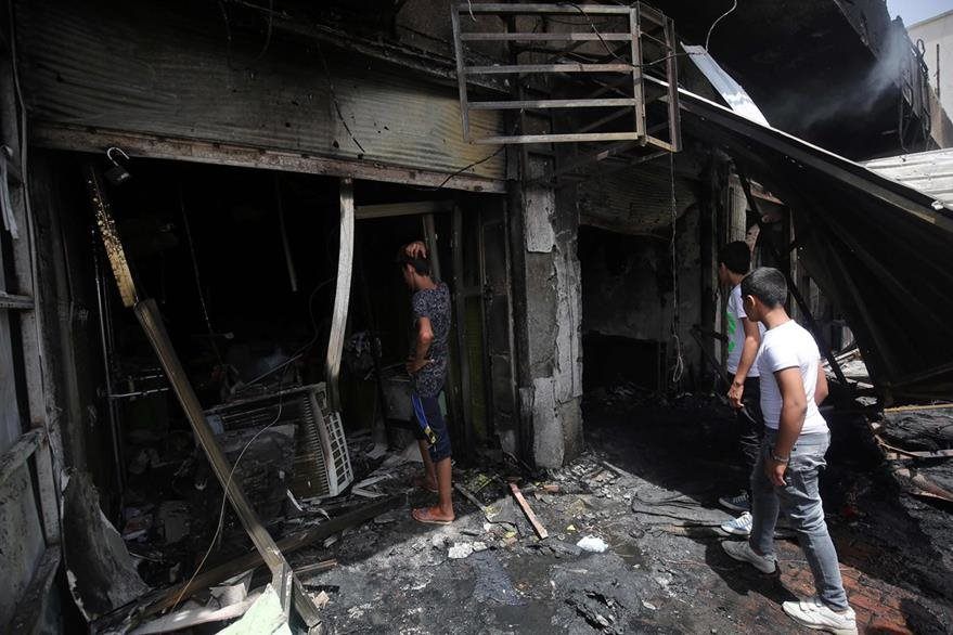 Dos iraquíes observan un inmueble destruido por uno de los atentados. (Foto Prensa Libre: AFP).
