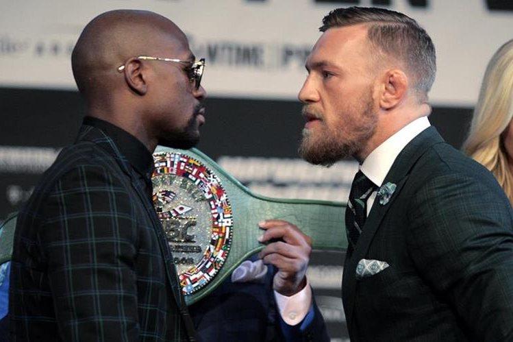 El boxeador Floyd Mayweather Jr. y el luchador de Connor Mcgregor, cara a cara durante la conferencia de prensa de este miércoles. (Foto Prensa Libre: AFP)