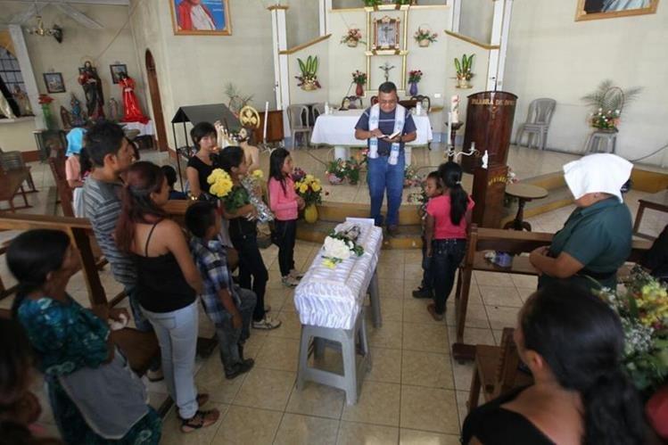 Familia y vecinos asisten a los oficios religiosos previo al sepelio del bebé, en San Pedro Ayampuc. (Foto Prensa Libre: Érick Avila)