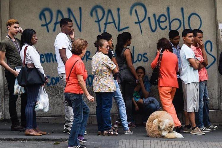 Venezolanos hace fila para tratar de comprar algo de pan en Caracas. (Foto Prensa Libre: AFP)