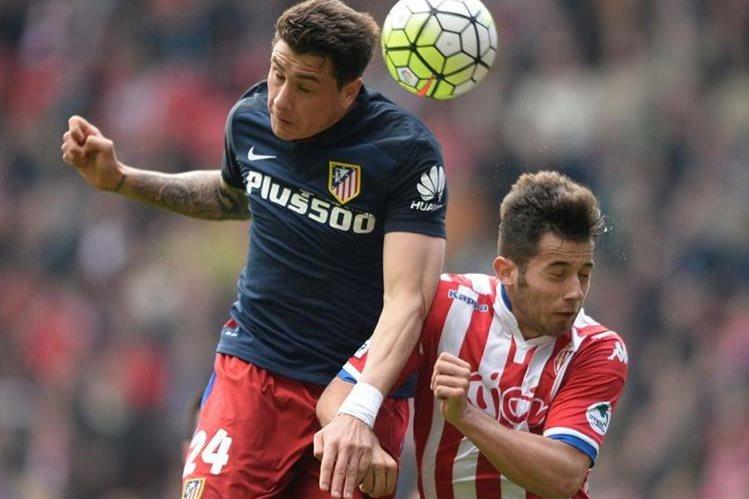 José María Giménez pelea el balón con Jony del Sporting Gijon durante el partido de este sábado. (Foto Prensa Libre: AFP)