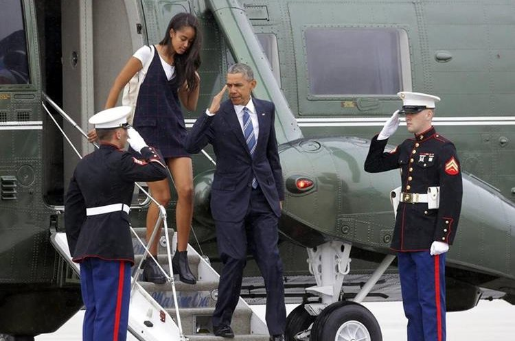 President Barack Obama, followed by his daughter Malia, returns a salute as they leave Marine One and head for Air Force One at Los Angeles International Airport, enroute to San Francisco in the middle of a two-day fundraising swing through California Friday, April 8, 2016. (AP Photo/Nick Ut)