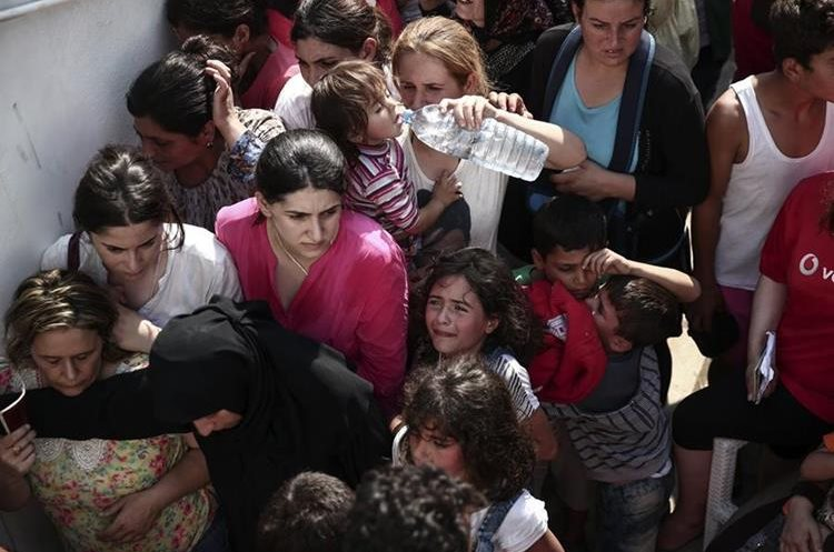 A girl cries as hundreds of migrants gather for a registration procedure at the stadium of Kos town, on the southeastern island of Kos, Greece, Tuesday, Aug. 11, 2015. Fights broke out among migrants on the Greek island of Kos Tuesday, where overwhelmed authorities are struggling to contain increasing numbers of people arriving clandestinely on rubber dinghies from the nearby Turkish shore.  (AP Photo/Yorgos Karahalis)