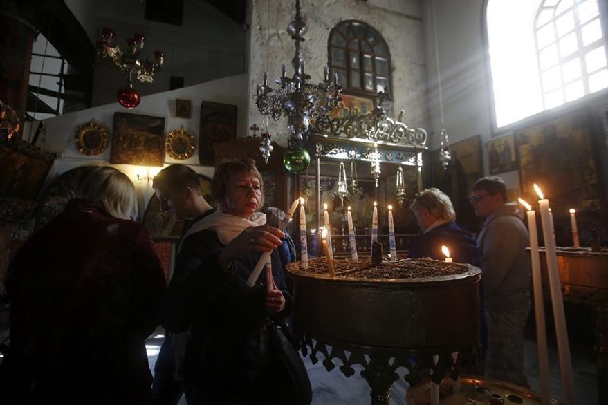 Cristianos ortodoxos encienden velas en la Basílica de la Natividad, en Belén. (EFE)