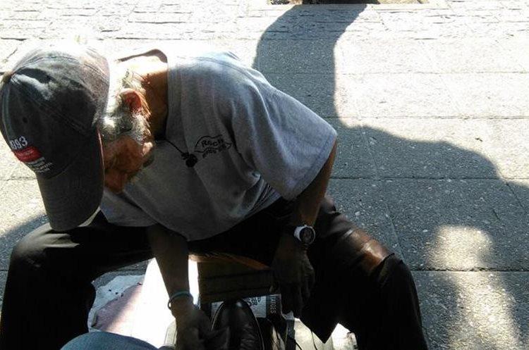 Édgar Augusto Polanco tiene 65 años y 57 de lustrar zapatos en el parque central, zona 1. (Foto Prensa Libre: Oscar García).