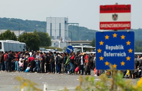 Refugiados esperan los autobuses después de llegar a la frontera entre Austria y Hungría.