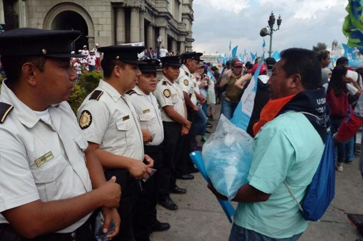 Un manifestante se acerca a los agentes de la Policía Nacional Civil para obsequiarles bolsas con agua pura.