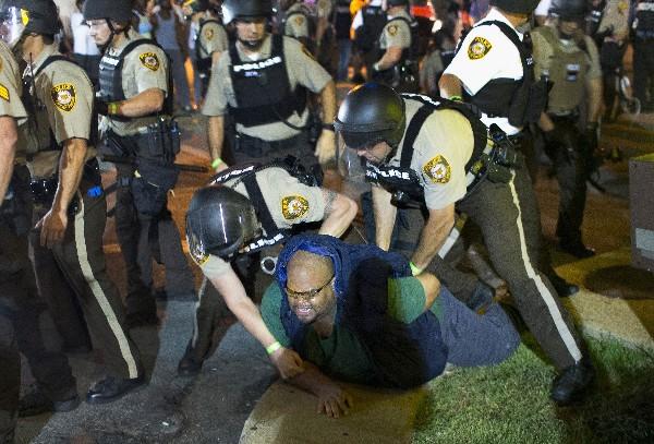 """<em><span class=""""hps"""">Un manifestante</span> <span class=""""hps"""">es arrestado</span> <span class=""""hps"""">durante la protesta</span> en Ferguson.</em>"""