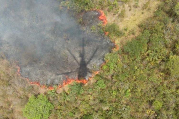 Desde un helicoptero lanzan agua a uno de los incendio en Petén. (Foto Prensa Libre: cortesía Conap)