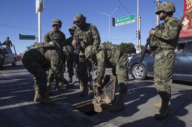 Mexican marines inspect a manhole where high-powered weapon were found to be abandoned, in the neighborhood where special forces had located the world