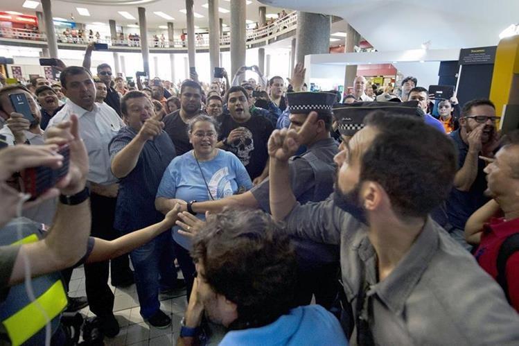 Opositores (i) y simpatizantes (d), de Lula da Silva cruzan insultos frente a la sede de la Policía de Sao Paolo donde el expresidente prestó declaración. (Foto Prensa Libre; AFP).