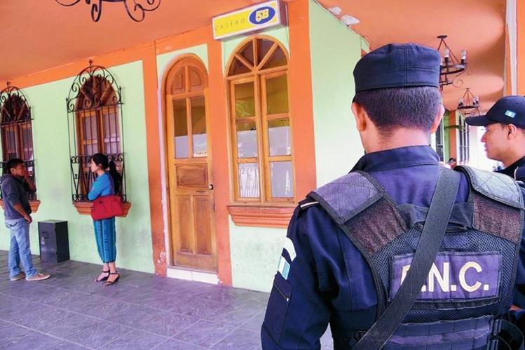 Agentes de la PNC prestan seguridad a cuentahabientes. (Foto Prensa Libre: José Rosales)