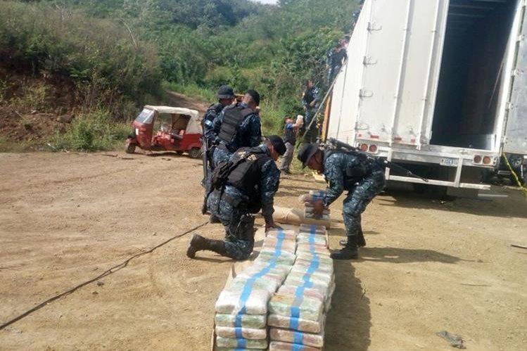 Agentes antinarcóticos examinan y contabilizan los paquetes hallados en un furgón, interceptado en Zacapa. (Foto Prensa Libre: PNC)