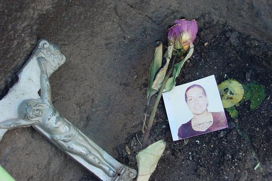 Un crucifijo roto y una fotografía eran portadas por un indocumentado. (Foto Prensa Libre: EFE).